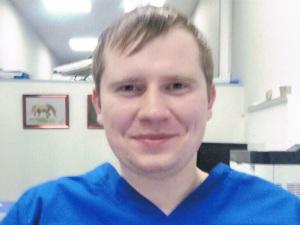 на фото молодой врач онколог в хирургическом костюме, зовут Москвичев Илья Игоревич